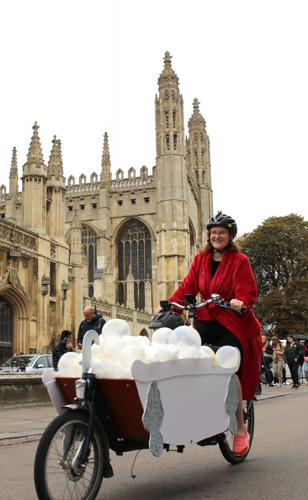 A cargo bike rides past King's College, Cambridge